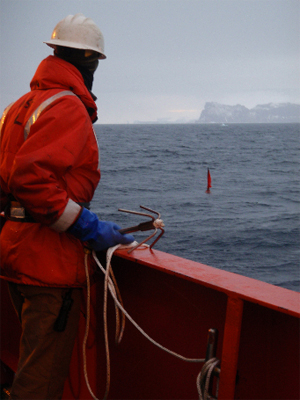 Ross Hein prepares to snag the floating whalebone lander (red flag) with a grappling hook.