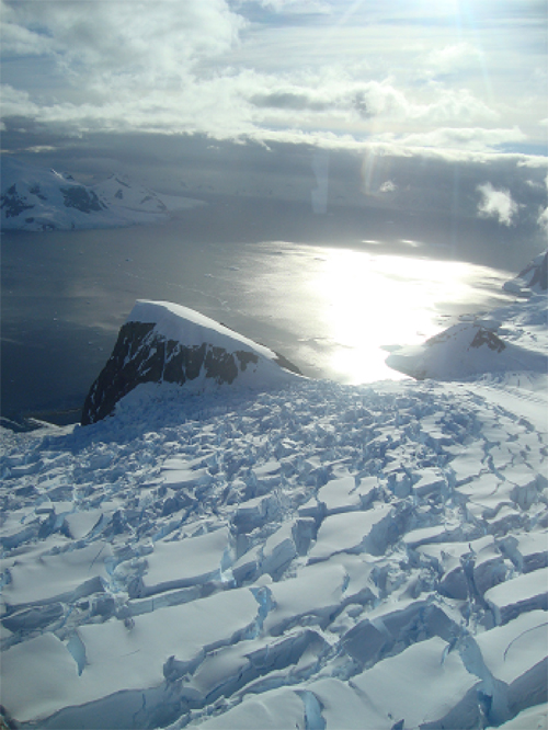 Aerial view of a glacier cascading (slowly) into Andvord Bay.