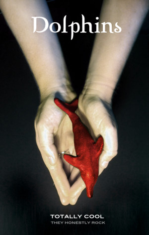 Photo of outstretched hands holding a red dolphin.