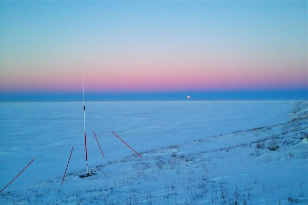 The HF radar transmit tower watches over the frozen Chukchi Sea at Point Lay. We mark 'em with bright orange reflective tape so snowmobilers don't hit them.