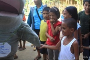 Waddy the dolphin meeting the kiddies in a village in Malampaya Sound, Philippines, at an outreach event Source: T.Whitty